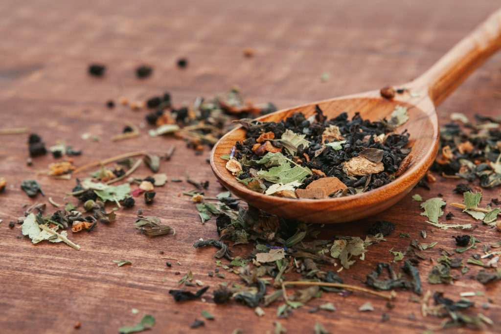 Black tea with herbs in wooden spoons on a wooden board