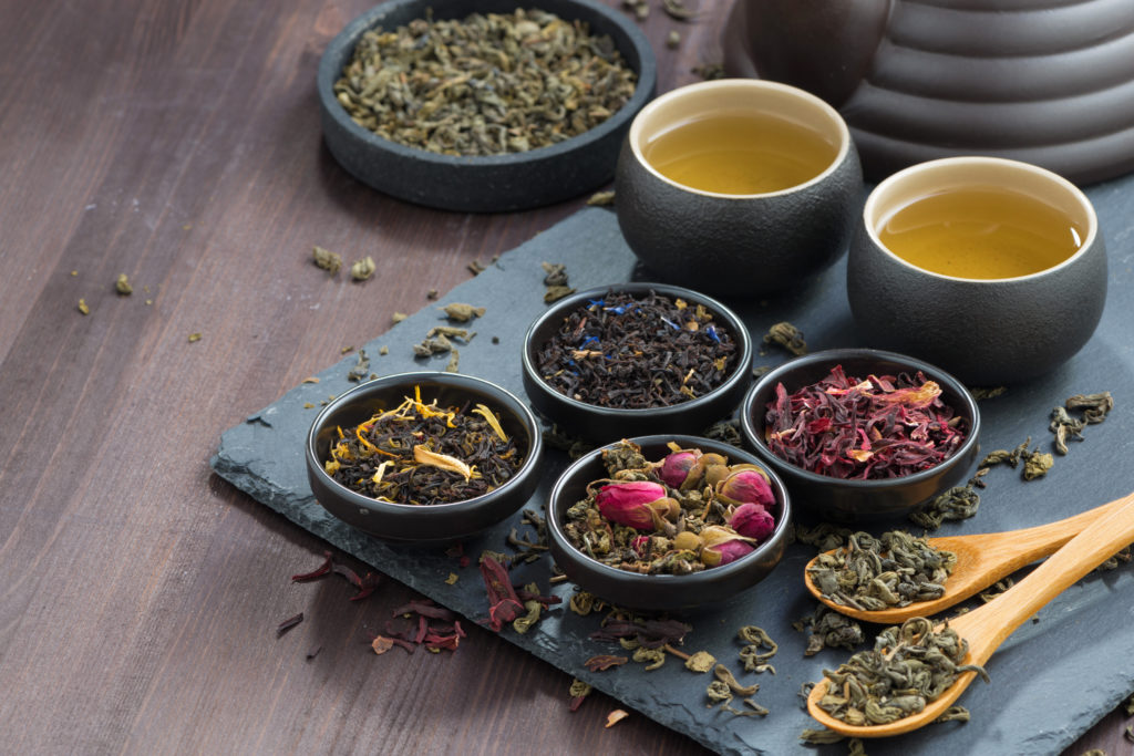 assortment of fragrant dried teas and green tea on wooden table, horizontal, close-up