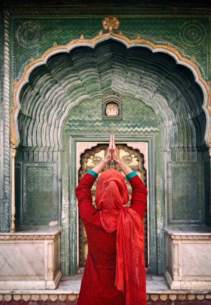 Indian Woman in red scarf with hands in prayer gesture at green gate door in City Palace of Jaipur,  Rajasthan, India. Space for your text, can be used as book or magazine cover.